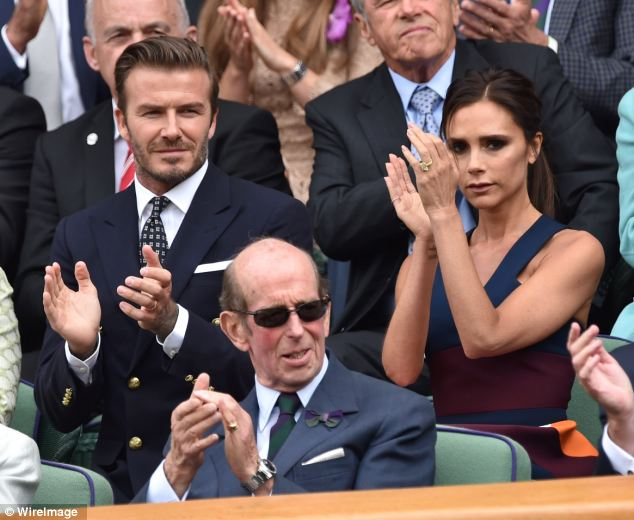 Enjoying the game? David (L) and Victoria (R) Beckham clap during the men's final at Wimbledon, but Victoria looks far from happy