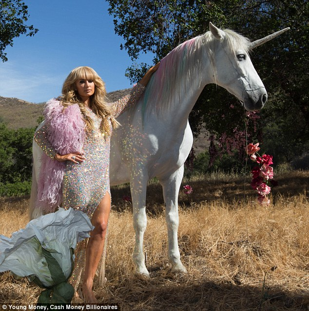 Me and my unicorn: The DJ glowed in a white sequined dress and pink boa as she stood next to an oak tree for the Come Alive video