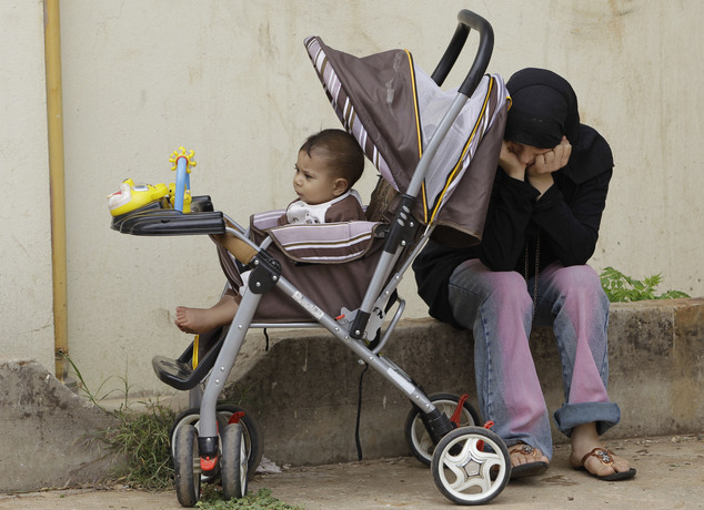 FILE - In this Wednesday, May 30, 2012, file photo, a Syrian refugee woman, who fled her house from the Syrian town of Tal-Kalakh, sits next to her baby at a...