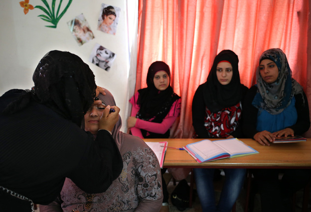 In this photo taken on May 29, 2014, Syrian refugee women, background, attend a make-up class where they obtain crucial training to find jobs in a community ...