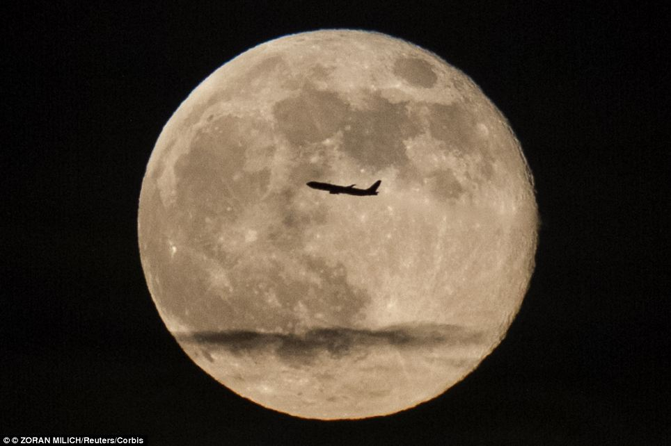 A silhouetted airplane flies past a 'super moon' over New York on June 23, 2013.