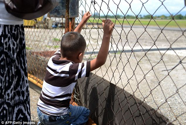 Watching their return: A boy watches as the plane carrying the 40 deportees taxis at the San Pedro Sula airport. The flight was the first of many according to immigration officials