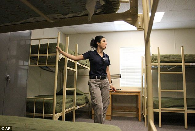 Overflow: Barbara Gonzalez, public information officer for Immigration and Customs Enforcement, shows a dormitory where immigrant families are housed at the Artesia Residential Detention Facility inside the Federal Law Enforcement Center in Artesia, New Mexico