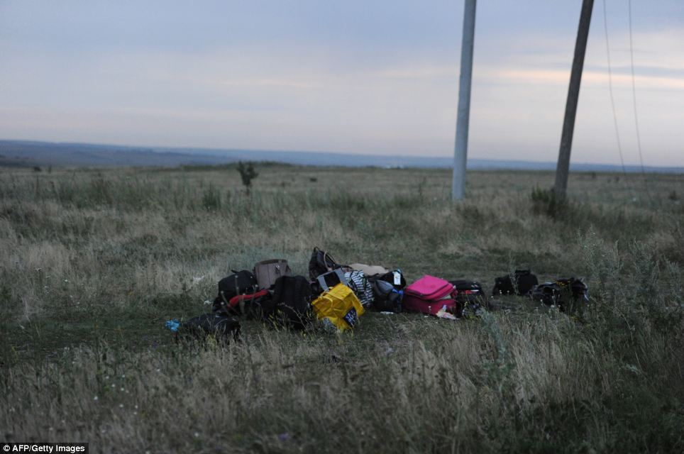 Discarded: Luggage from the plane is piled up at the crash site by rescue workers performing recovery work in east Ukraine