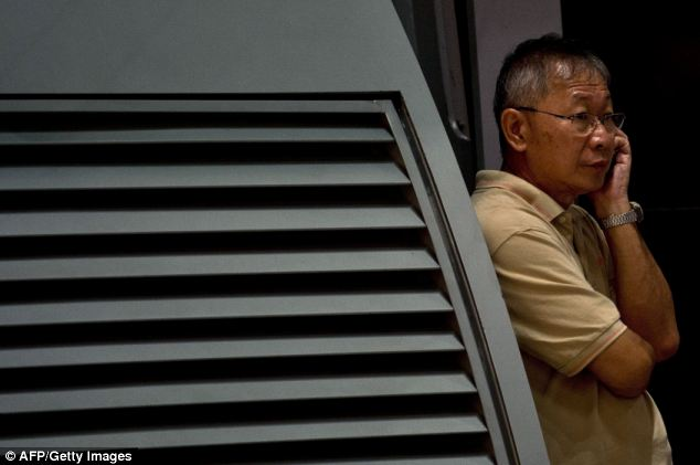 A relative of passengers onboard Malaysia Airlines flight MH17 from Amsterdam speaks on the phone as he waits for information outside the family holding area at the Kuala Lumpur International Airport