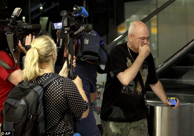 A relative of a passenger on flight MH17 walks past members of the press as he arrives at Schiphol airport in Amsterdam, to find out more information