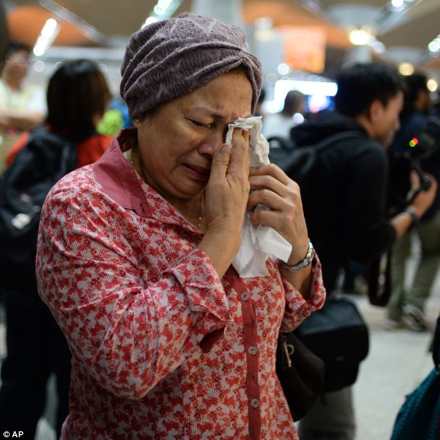 A woman weeps into a tissue after hearing news regarding a relative who was travelling on the plane. She was one of a group of people who gathered in Kuala Lumpur International Airport early on Friday morning local time