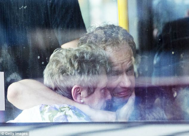 A tearful couple, who had loved ones on board flight MH 17, hold on to each other for support as they leave Schiphol airport on Thursday evening