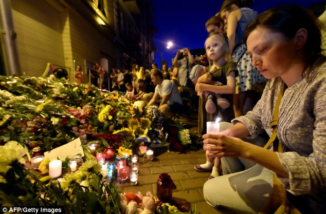 A woman lights a candle in front of the Embassy of the Netherlands in Kiev on Thursday night to commemorate passengers of Malaysian Airlines flight MH17