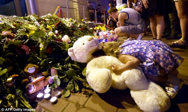 A young girl places her head on a teddy bear as people around her light candles at the Embassy of the Netherlands in Kiev. They gathered on Thursday night to pay tribute to those on flight MH17