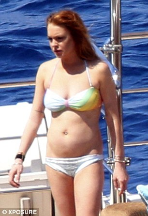 A tale of two yachts: Lindsay Lohan enjoys a cigarette in Capri, while Elle Macpherson (22 years older) suns her hot bod in Sardinia