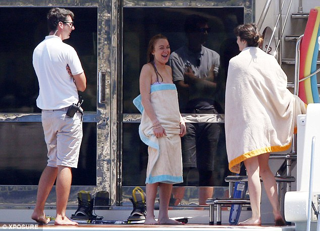Hilarious: She shares a joke with pals after wrapping herself up in her beach towel