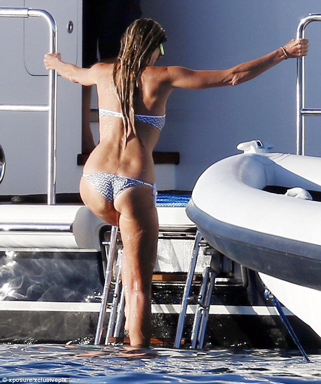 Getting out: She even showed off her toned arms as she grab hold of the yacht to pull herself up
