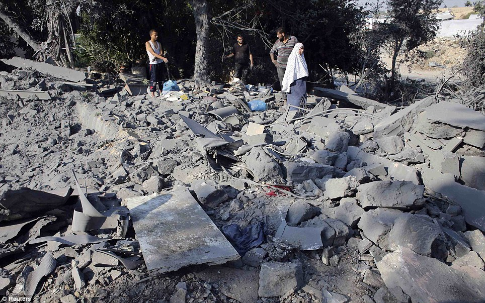 Palestinians look at the rubble of a house which police said was destroyed in an Israeli air strike in Rafah, in what appeared to be the heaviest since Israel launched its offensive on the Palestinian territory on July 8