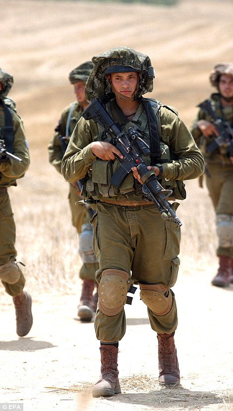 Israeli soldiers hold positions at an army deployment near the Israeli-Gaza border after militants from Gaza infiltrated southern Israel through two tunnels