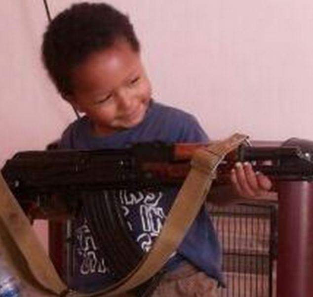 Chilling: A child smiles as he poses with an AK-47 assault rifle in an image posted online by his British mother