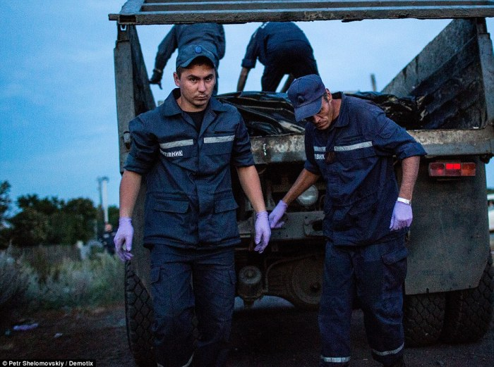 Horrifying: The bodies are dumped in rubbish trucks by rescue workers. Despite criticism, militiamen insist they are doing everything they can for the dead