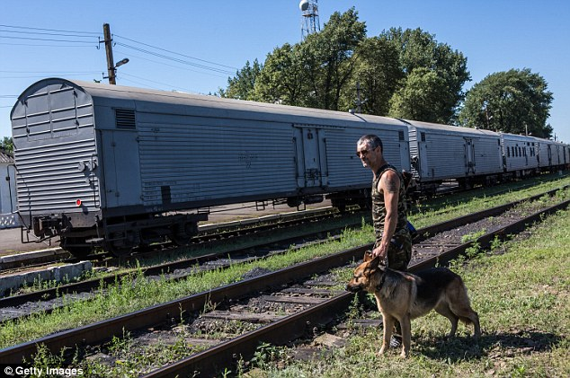 Grisly: The bodies of almost 200 victims of the MH17 plane disaster were seen for a fourth day in a refrigerated train which has done little to hold back the stench of decay which has already overtaken the corpses