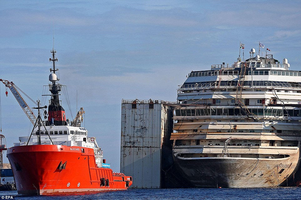 The heavy tug boat Blizzard (left) moves into position to maneuver the re-floated wreck of the Costa Concordia cruise liner from its position off the coast of Giglio. The operation to get it moving again began today