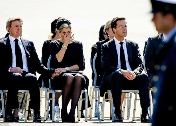 Upset: Queen Maxima of the Netherlands (pictured centre alongside her husband King Willem-Alexander) wipes away a tear as the bodies of victims of the MH17 crash are removed from an air force transport plane and placed in hearses at Eindhoven airport