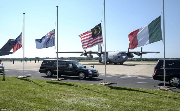 Flags - including that of Malaysia (centre) were seen flying at half mast as the convoy of hearses made their way from Eindhoven military air base
