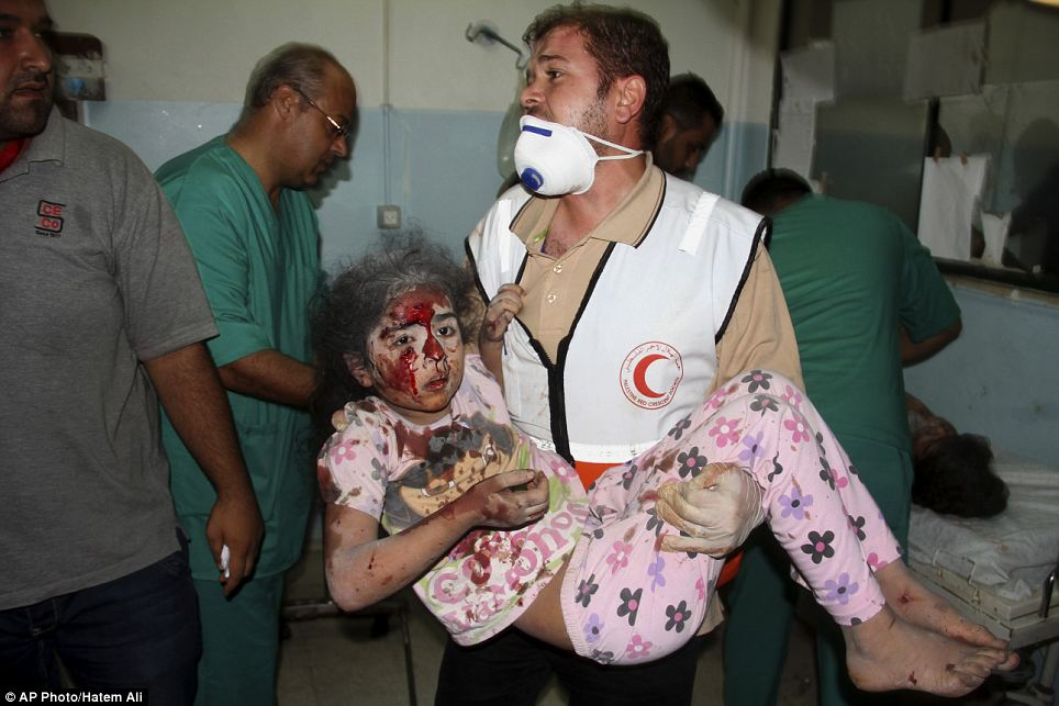 A Palestinian medic carries a wounded girl to a treatment room of Nasser hospital, following an Israeli airstrike hit her home in Khan Younis
