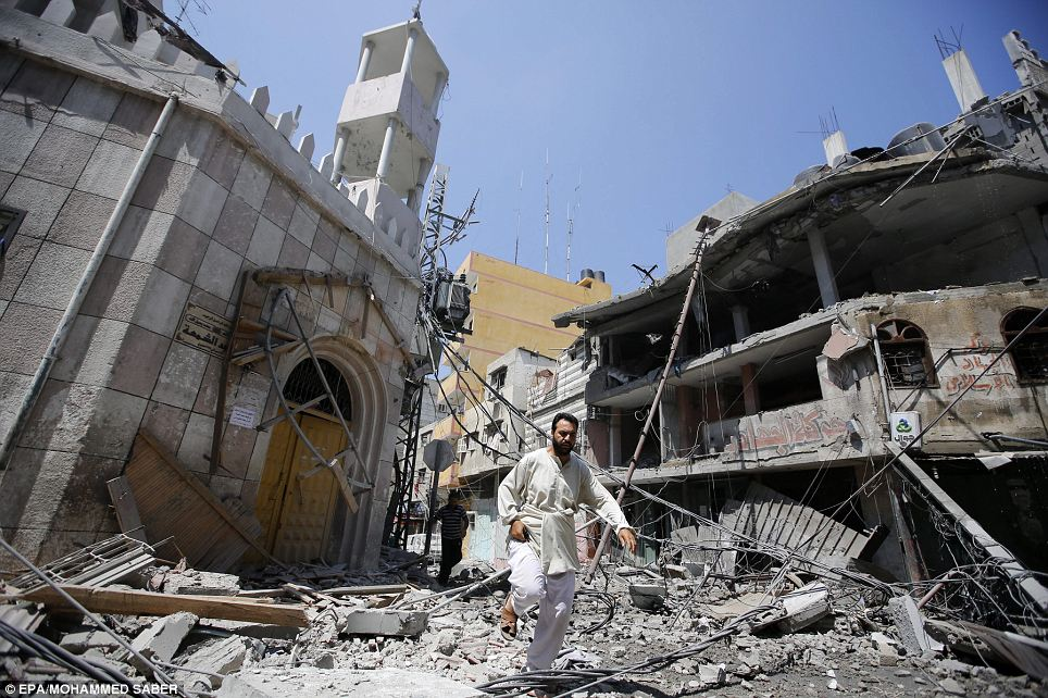 A man runs for cover during Israeli air strikes in Gaza City, which have killed nearly 650 Palestinians in two-and-a-half weeks