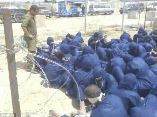 Imprisoned: Following their capture, the suspects were forced to wear blue overalls, before being blindfolded and made to sit in a small enclosure with barbed wire fencing. Above, a soldier watches over the suspects