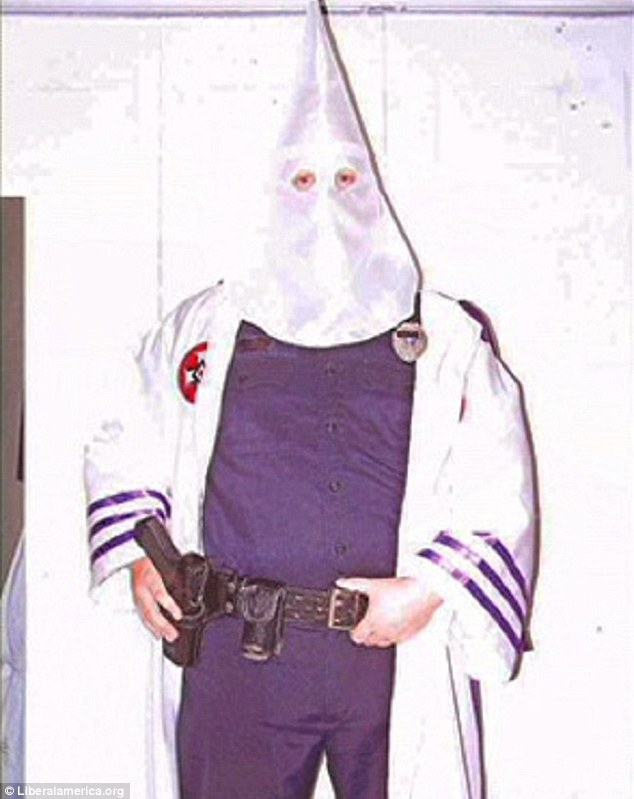 Shock: Fruitland Park police officer James Elkins resigned in 2009 after being outed as a KKK Kleagle - or recruiter - when this picture emerged of him in KKK hood with his uniform, badge and gun. Elkins informed on another cop, George Hunnewell, and his wife who he claimed were with him at a induction ritual that year