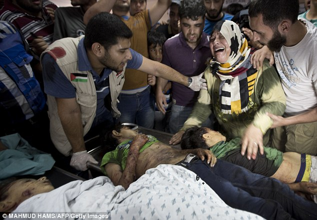 A mother wails over the bodies of children killed in an attack on a refugee camp playground in Gaza City
