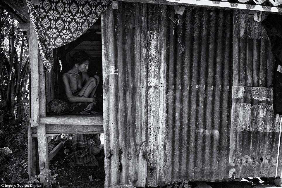 Esta pequena gaiola de metal longe da casa principal tem sido a prisão de Sari há mais de 16 anos, quando ela ficou doente mentalmente ela foi colocada nesta lata galpão com apenas um piso de bambu tecido para sentar.  Aqui, ela está sentada em uma posição quase não mudou ao longo de todos esses anos.  Agora, ela não é capaz de andar mais