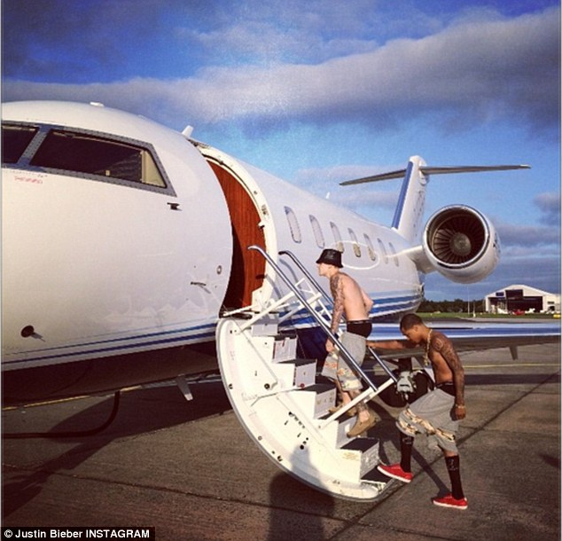 On his way to Spain: Bieber seen boarding his jet with no shirt on as a pal was behind him