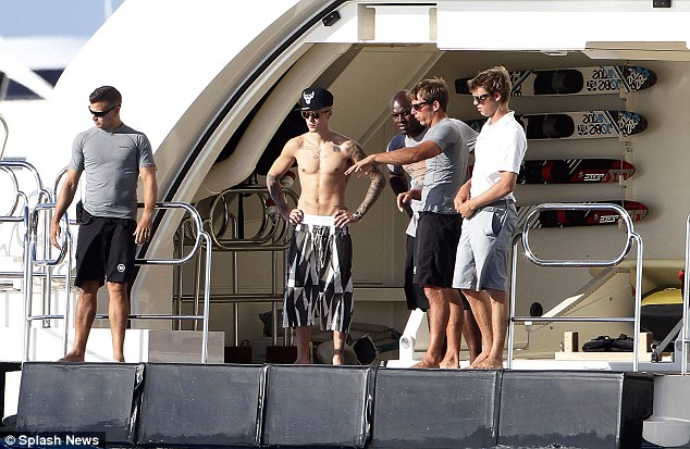 Keeping it long: Justin wore a very long pair of swim shorts which swamped him