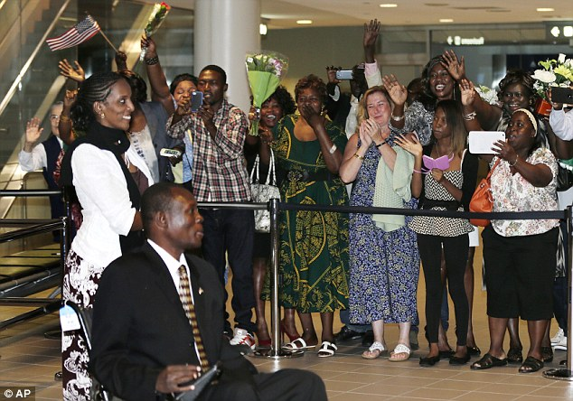 Return: Meriam Ibrahim, left, and her husband, Daniel Wani, of Sudan, are greeted by family and friends shortly after arriving in Manchester, New Hampshire, Thursday, July 31, 2014