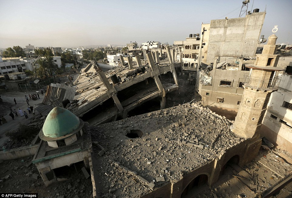 Strikes: The historic al-Omeri mosque in the nearby city of Jabalia was also damaged by an Israeli strike overnight, though its ancient minaret (right) remained intact