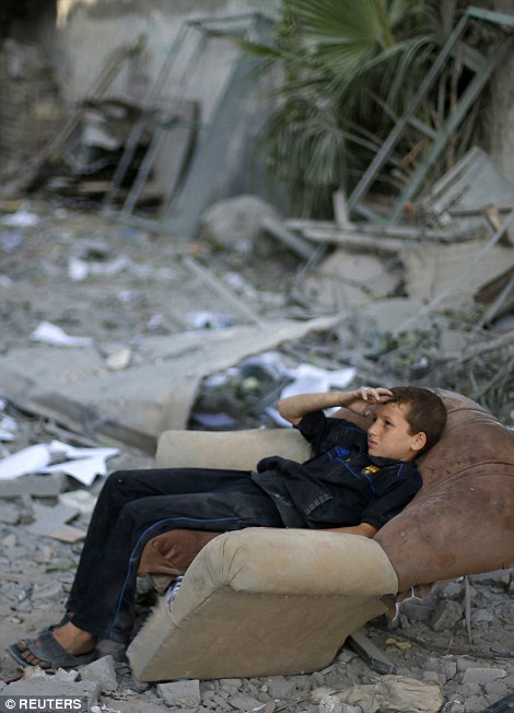 A Palestinian boy sits in a sofa outside his family's house, which witnesses said was damaged in an Israeli air strike, in Gaza City