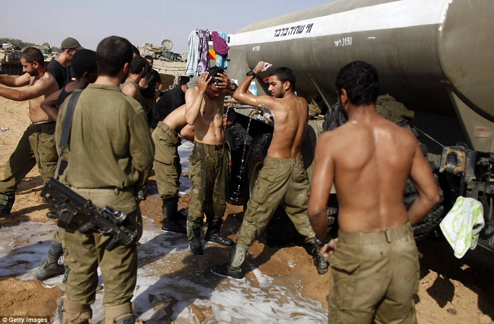 Exhausted: Israeli soldiers wash themselves this morning at a deployment area on Israel's border with the Gaza Strip. They were still searching for the missing soldier