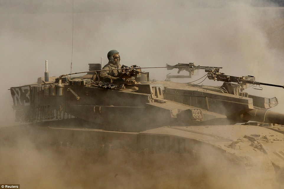 War: An Israeli soldiers rides a moving tank near the border with Gaza. What began as a series of air strikes has escalated into a ground incursion over recent weeks
