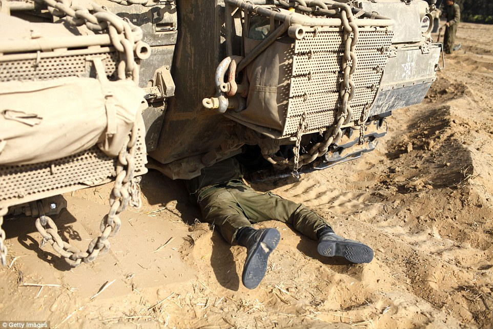 Taking stock: An Israeli soldier carries out maintenance on his tank as troops prepare for another deployment on the border with the Gaza Strip this morning