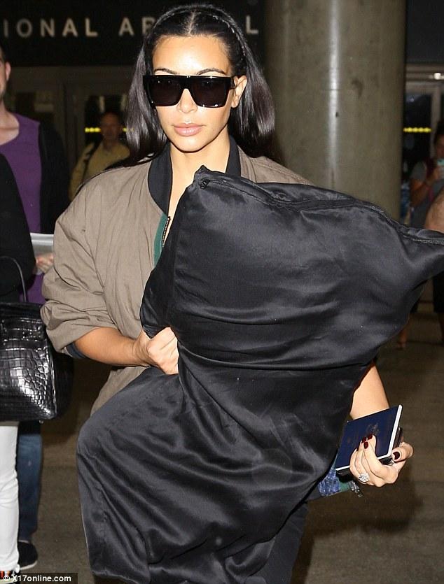 Kim Kardashian totes large silk pillow as she arrives back