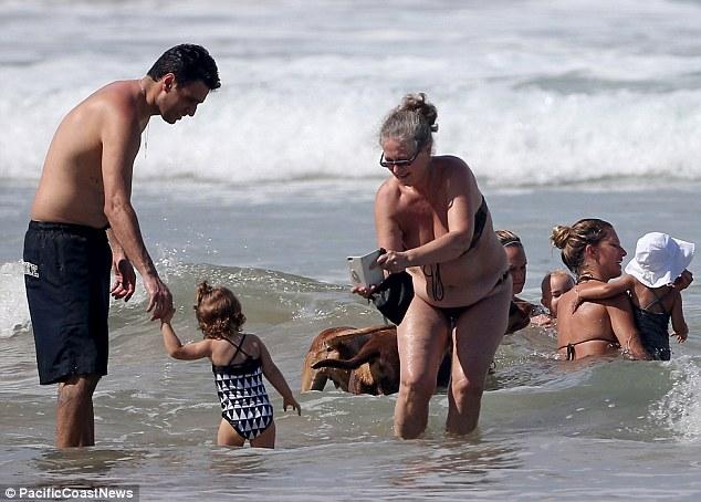 Caso de família: Uma mulher que parecia ser a mãe de Gisele Vania foi visto tirando uma foto de outra criança na água enquanto Gisele tomou um mergulho com Vivian
