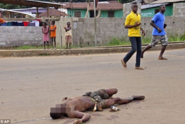 Abandoned: The body of a man who has been infected with the Ebola virus lies dead in the streets of Liberia