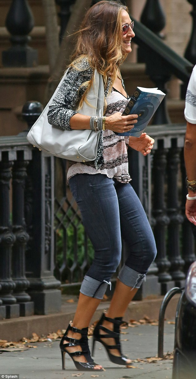 Sarah Jessica Parker leaving her home carrying novel The