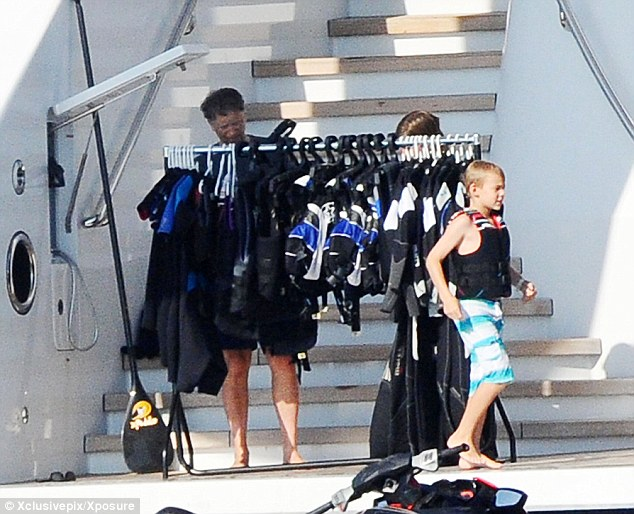 Which wetsuit? Bill Gates looks for suitable gear to wear for a jetski while his son, Rory, runs past him
