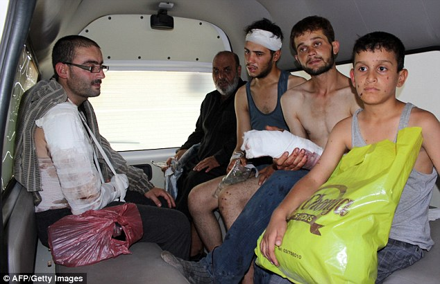 Hurt: Injured Syrians are seen inside a van. They hope to be safer inside their own country