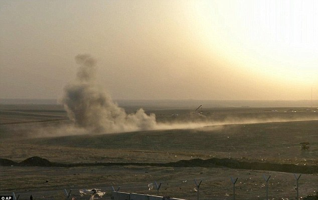 Gone in a cloud of smoke: A dust cloud rises where the first U.S. bomb struck ISIS artillery being towed by a truck outside Erbil