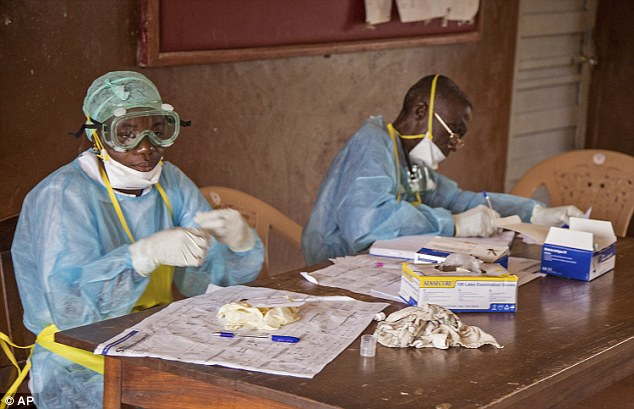 Health workers wearing protective clothing and equipment sit at a desk at the Kenema Government Hospital