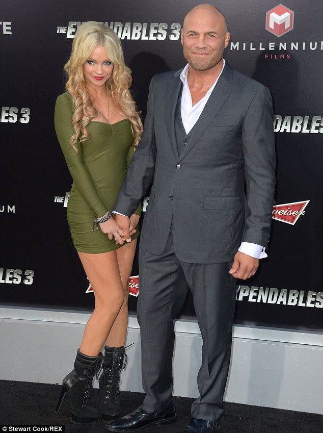 Blonde companion: Randy Couture attended the premiere with a blonde companion in a green minidress