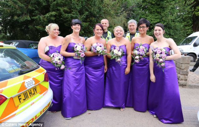 A festa nupcial posando com os policiais úteis que eles garantiram alcançou o casamento na hora