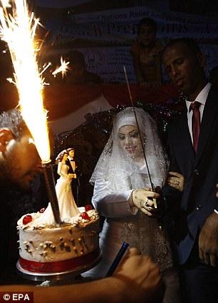 Les jeunes mariés même manged à poser pour des photos à côté d'un gâteau de mariage à trois niveaux avec des cierges magiques